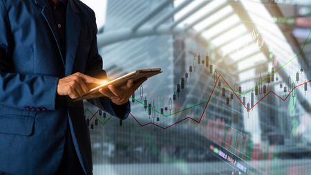 Businessman finger touching tablet with finance and banking profit graph of stock market trade indicator financial 版權商用圖片