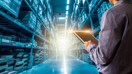 Biznesmen menedżer za pomocą tabletu sprawdzania i kontroli dla pracowników z logistyką magazynową Modern Trade. Koncepcja Przemysłu 4.0