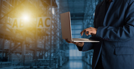 Businessman manager using laptop check orders online goods worldwide for network with Modern Trade warehouse logistics. Industry of logistics network concept. Foto de archivo