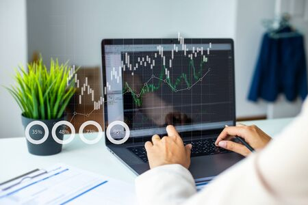 Female Analyst and desk work on a Laptop Showing Statistics, Graphs and Charts. on the wooden table in Office. Banque d'images - 132216746