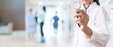 Doctor with stethoscope in hand and Patients come to the hospital background. Medical healthcare staff and doctor service.