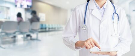 Doctor hand touching on tablet computer in hospital office. Medical healthcare staff and doctor service.