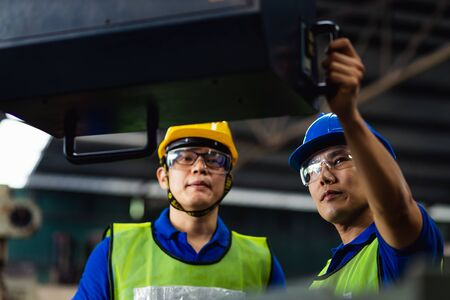 Staff engineers in uniforms and safety helmet of yellow are inspecting work and the job training he works in factory industrial machinery.