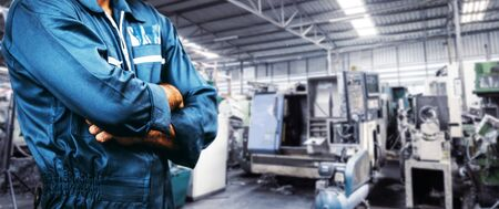 The image Engineer men working in a manufacturing plant for background of industry. men is standing with arms folded in a storage facility or warehouse. men is wearing a uniform safety vest. Stock Photo