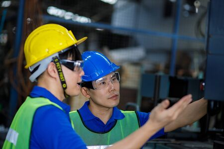 Asian Engineer and staff or Industrial worker talking production line machine and setting it for work in modern factory.