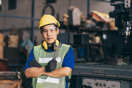 Portrait of industrial engineer wearing a yellow helmet while standing in a heavy industrial factory behind 版權商用圖片