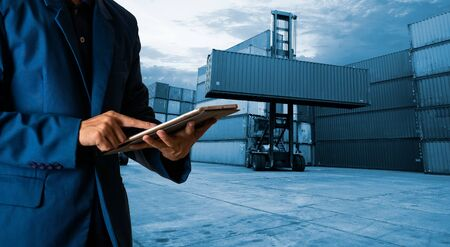 Businessman manager touching tablet check and control for workers with container, working crane for business logistics. logistic import export and transport. international global ship. 免版税图像