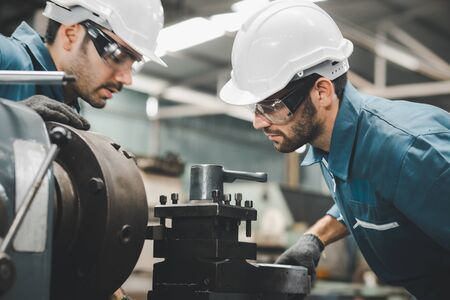 Two maintenance engineers discuss inspect relay checking machinery and repair system in a factory. They work a heavy industry manufacturing factory.