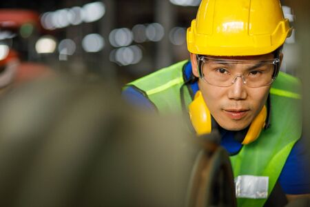 Professional asian worker engineer wearing a yellow helmet while standing in a heavy industrial he looking of working at industrial machinery and check security system setup in factory. 免版税图像