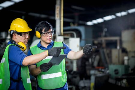 Two asian maintenance engineers discuss inspect relay checking information and protection system on a tablet computer in a factory. They work a heavy industry manufacturing factory.