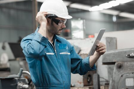 Maintenance engineer industrial plant with a tablet in hand and document plan, Engineer looking of working at industrial machinery setup in factory.
