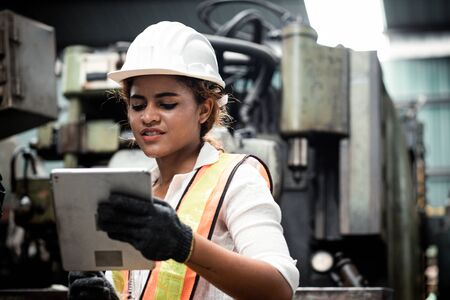 Close up hand industrial industrial plant with a tablet in hand, Engineer looking of working at industrial machinery setup in factory.