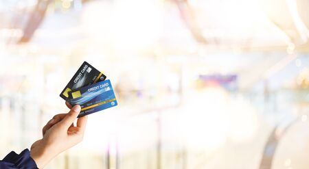 Close up of hand woman holding credit card for shopping with abstract blur mall background. Business shopping ideas concept. Web banner. 版權商用圖片