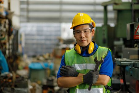 Portrait of industrial engineer wearing a yellow helmet while standing in a heavy industrial factory behind 免版税图像
