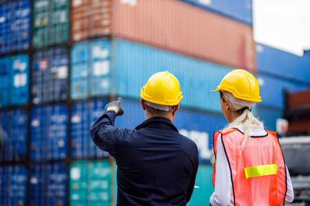 Warehouse shipping transportation concept. Commercial docks worker and inspector at commercial dock. Workers are wearing protective clothing they are standing against cargo containers.