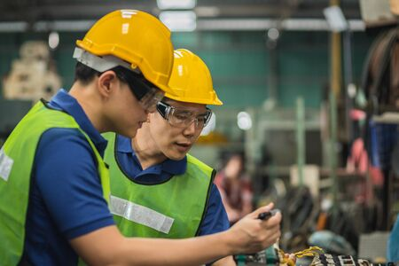Two men engineer talking in modern factory. Production line machine and setting it for work. 免版税图像