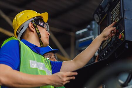 Two men engineer talking in modern factory. Production line machine and setting it for work. Men industrial engineer wearing a Yellow helmet while standing in a heavy industrial factory