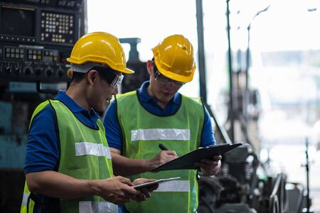 Industrial two men engineers in a factory checking documents 版權商用圖片