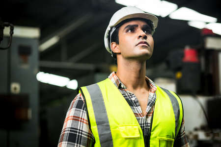 Industrial engineer in hard Hat wearing safety . He looking of works at Industry manufacturing factory. In the background welding / metalworking processes are in progress.