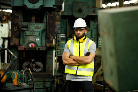 Serious male engineer is standing cross arms at metal lathe industrial manufacturing factory. He is wearing safety vest, hard hat and safety glasses.