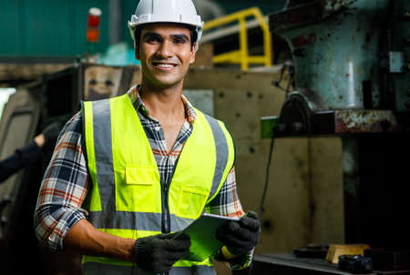 Portrait of smile male Indian engineer is holding the tablet while he standing and working in the heavy industry factory.