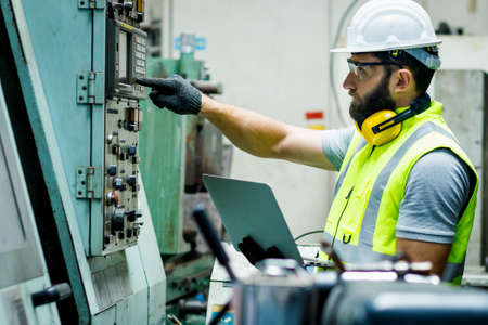 Mechanical engineer is pushing the button of the control panel while he is holding the laptop to check the list to set up in the control room at the factory.