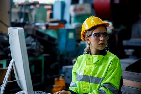 Female technician who wearing hard hat, safety glasses and safety shirt is listening the assignment while she is using the computer at the machine industrial factory.