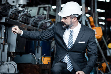 Chief engineer is sitting and checking the quality of the machine at the industry or factory before the engines are starting and running. He is wearing suit and hard hat.