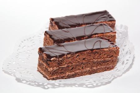 Three chocolate cake with cream and chocolate glaze on a lace napkin Stock Photo - 12221209