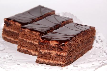 Three chocolate cake with cream and chocolate glaze on a lace napkin photo