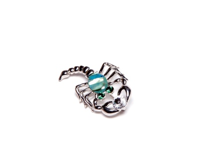 Brooch scorpion with emeralds and diamonds on a white background photo