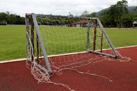 An old small football goal with tearing net locates in a football training field