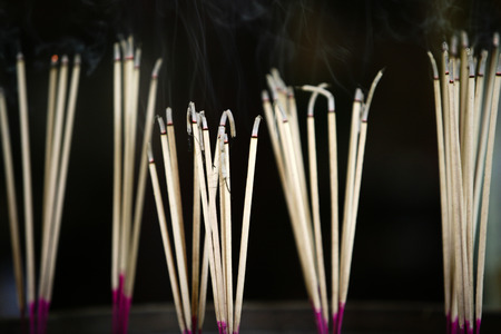The image of the incense burning and smoke for pay homage to holy thing along with the blurring in the background.