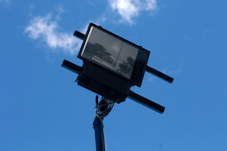 Photo of spotlight with a bright blue sky is the background.
