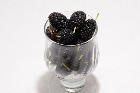 medium group of object: mulberries in a glass on a white background