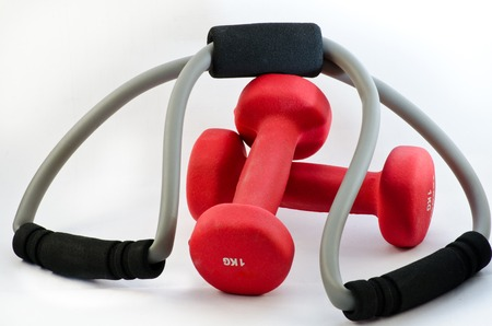 Two red dumbbells and rubber expander on a white background