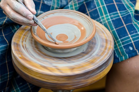 potters wheel: saucer made of clay on a potters wheel, a brush and paint