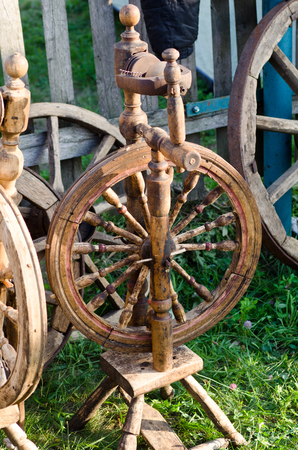 wooden spinning wheels on the grass in the evening light