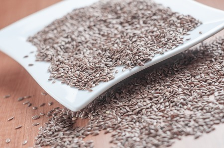 cathartic: White ceramic bowl full of hemp seeds over wood background Stock Photo