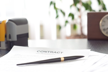 Contract on wooden desk with clock and fountain pen photo