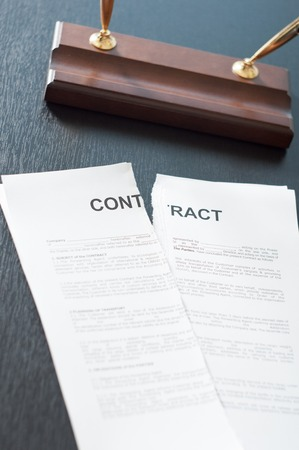 Terminate the contract on a black table with a pen photo