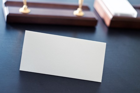 almanac: White triangular sign for the label standing on a table. Room for you text.