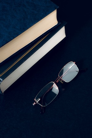 rimmed: a pile of books and glasses symbolizing the concept of reading habit or studying.