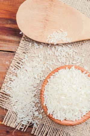 rice in a pot and spoon on burlap. photo