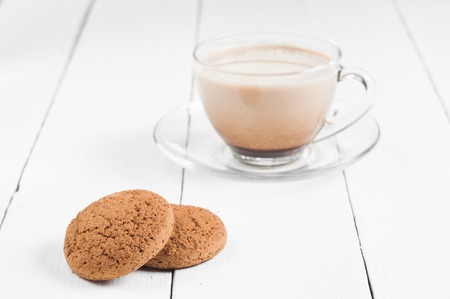 cikolatali: oatmeal cookie with coffee wooden white background.