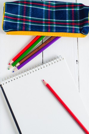 Blank paper and colorful pencils on the table. View from above. photo