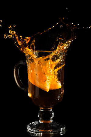 sputter: Stemmed glass with tea splashing out, close-up isolated on black