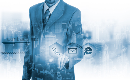 contact us icon: Businessman pressing virtual phone buttons. customer support concept. Stock Photo