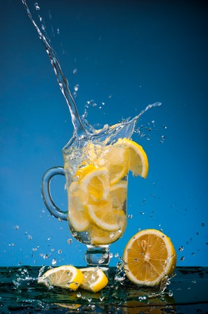 lemon slices: Lemon slices falling into a glass of lemonade and a big splash on a blue background.