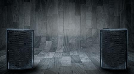 PARLANTE: Altavoces grandes negras sobre fondo de madera con espacio para escribir el texto.